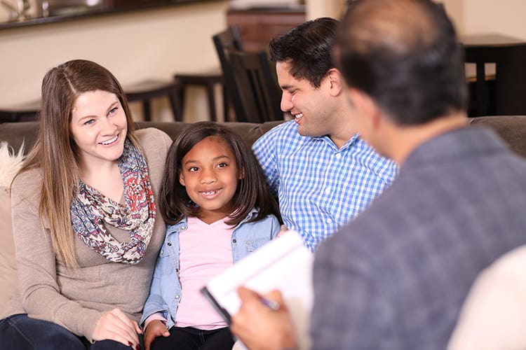 A couple with their adopted daughter talking to a representative from an adoption agency