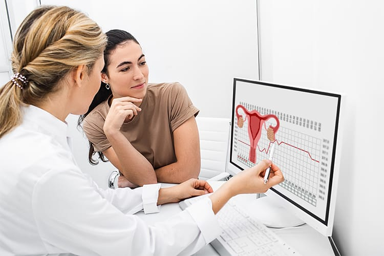 Nurse showing diagram of female hormone levels on a screen