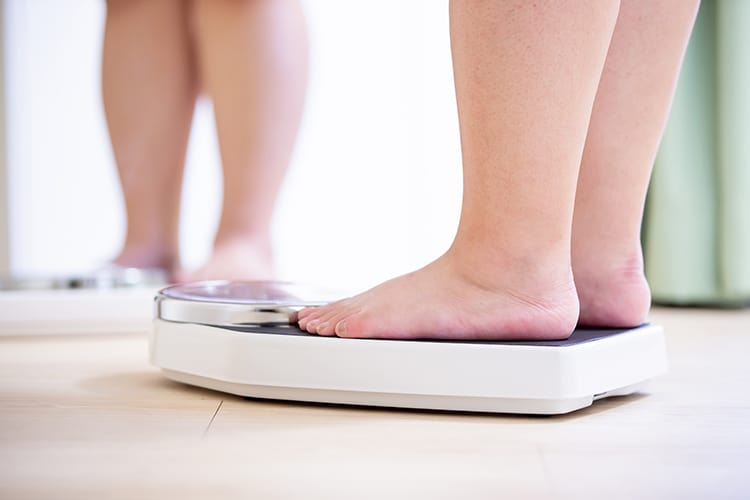 Woman on a weight - overweight may cause fibroids in the uterus
